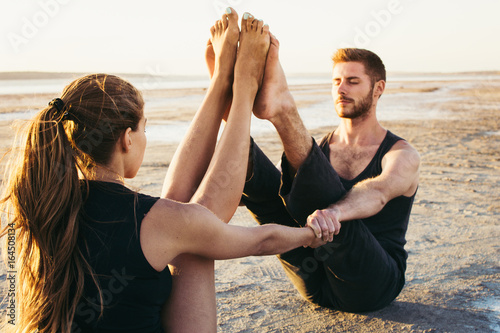 Young couple practicing yoga on beach at sunrise or sunset