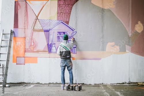 plakat Graffiti artist painting on the wall
