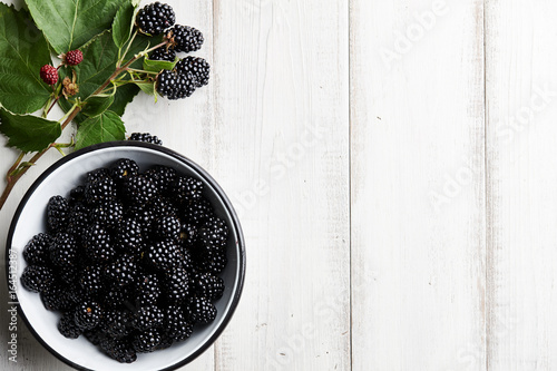 Bowl of fresh ripe blackberries on textured stone background