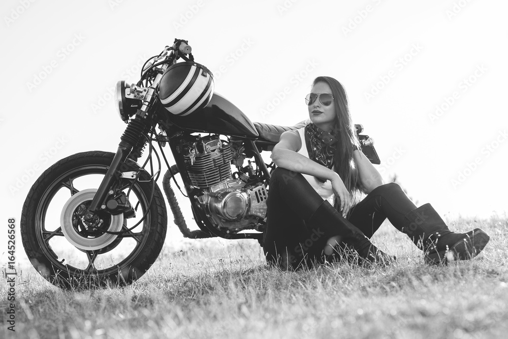 Fototapeta  Black-and-white portrait of a beautiful biker woman sitting by her motorcycle