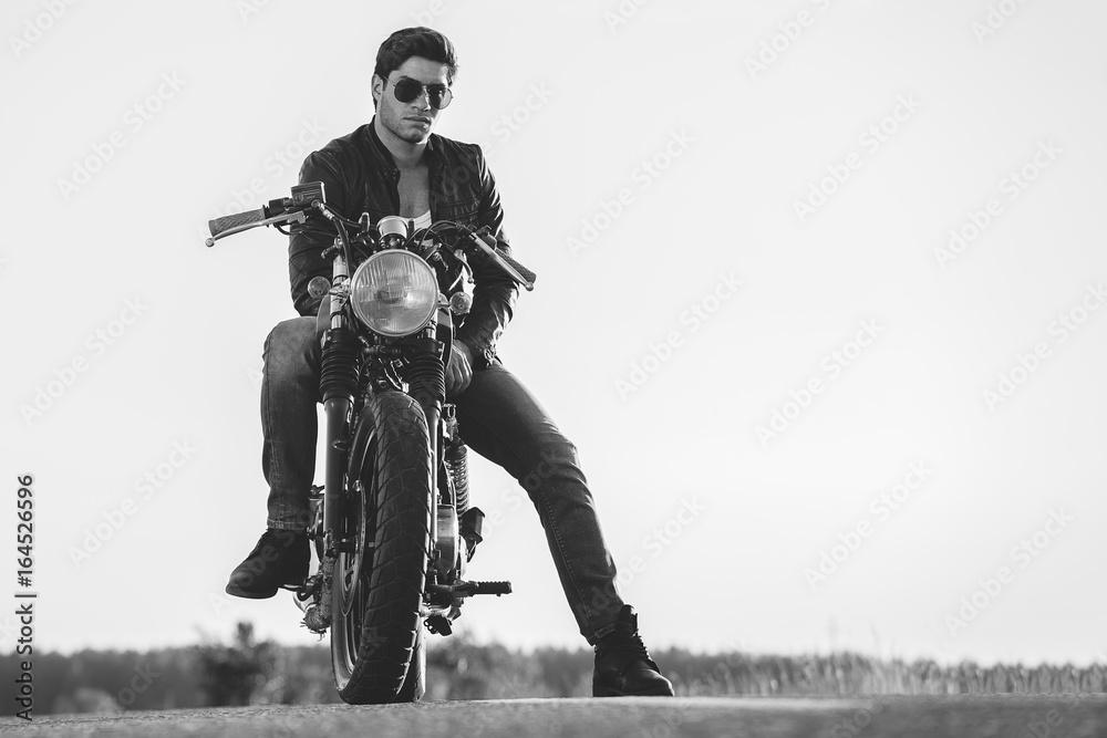 Fototapeta Biker man sits on a bike
