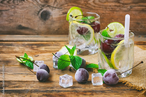 Two glasses with drink with straw, frozen cherries, lemon, lime and mint leaves