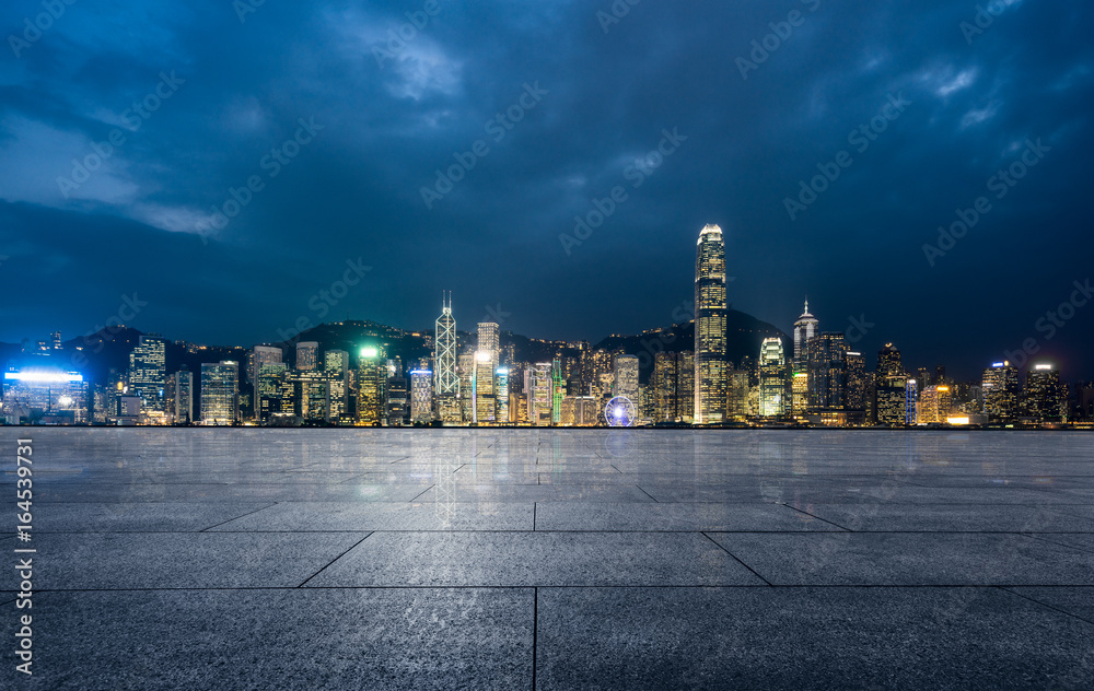 Fototapety, obrazy: empty brick platform with Hong Kong skyline in background at night.