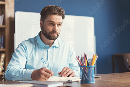 Fotografia, Obraz  Pensive bearded youthful guy doing employment test indoor