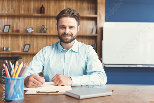 Vászonkép  Cheerful youthful bearded guy performing formal task in office