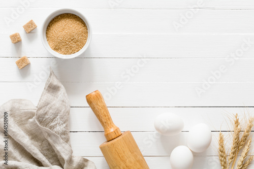 Baking ingredients: brown sugar, white eggs, rolling pin, and wheat on white wooden table. Top view, copy space