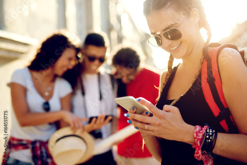 Young tourists searching for location both on mobile phone and map.