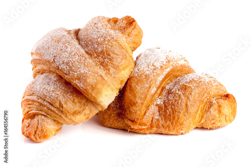 Fotografia two croissant sprinkled with powdered sugar isolated on a white background close