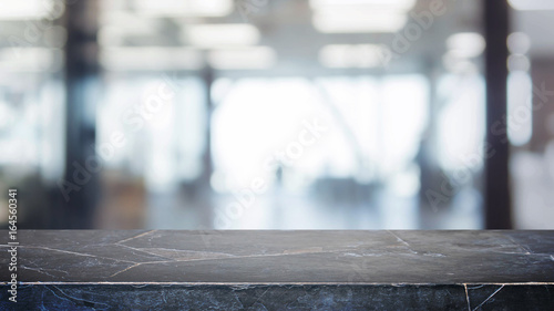 Fotografie, Obraz  Black stone table top and blurred bokeh office interior space background - can used for display or montage your products