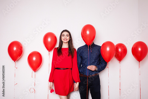 Photo  A loving couple holding hands and a guy covering his face with balloon on a whit