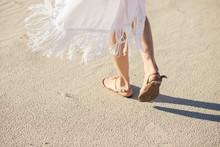 Female Legs In Sandals Go On A Desert Sand