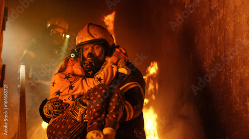 Brave Fireman Descends Stairs of a Burning Building and Holds Saved Girl in His Arms Canvas Print
