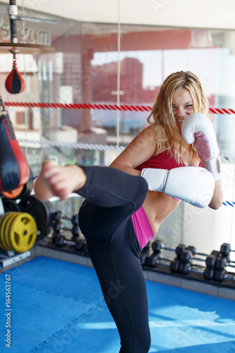Young martial artist woman kicking in gym into camera Canvas Print