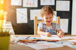 child  girl draws with colored pencils