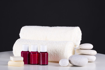 Obraz na płótnie Canvas Spa. White towels, stones and three bottles of cream, lie on a table, on a black background.