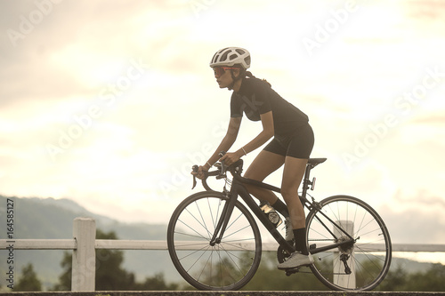 Asian healthy Cyclist girl wearing helmet Cycling and exercise on bicycle in sprint track and open road and cross process and soft flare filter work out and sport concept