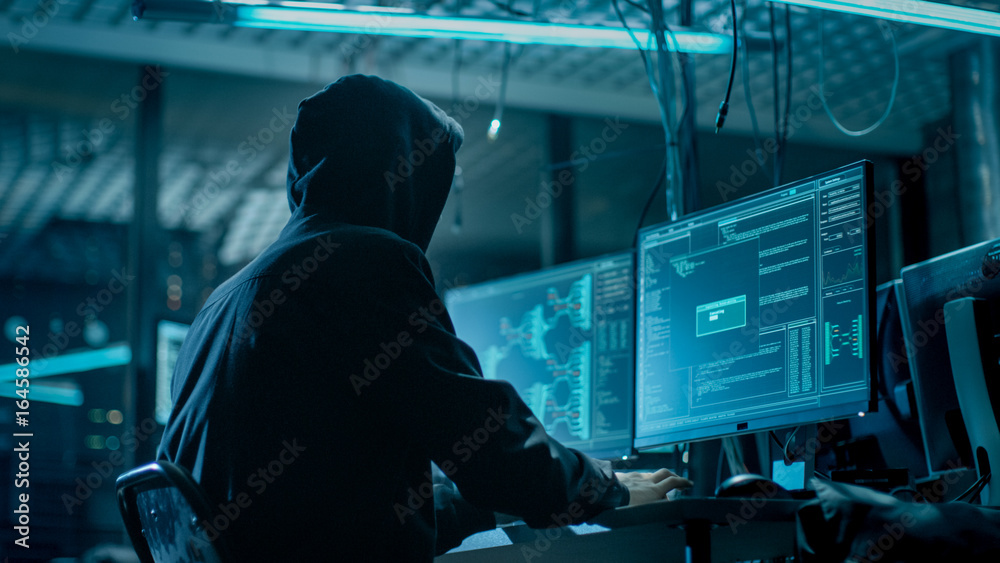 Fototapety, obrazy: Shot from the Back to Hooded Hacker Breaking into Corporate Data Servers from His Underground Hideout. Place Has Dark Atmosphere, Multiple Displays, Cables Everywhere.