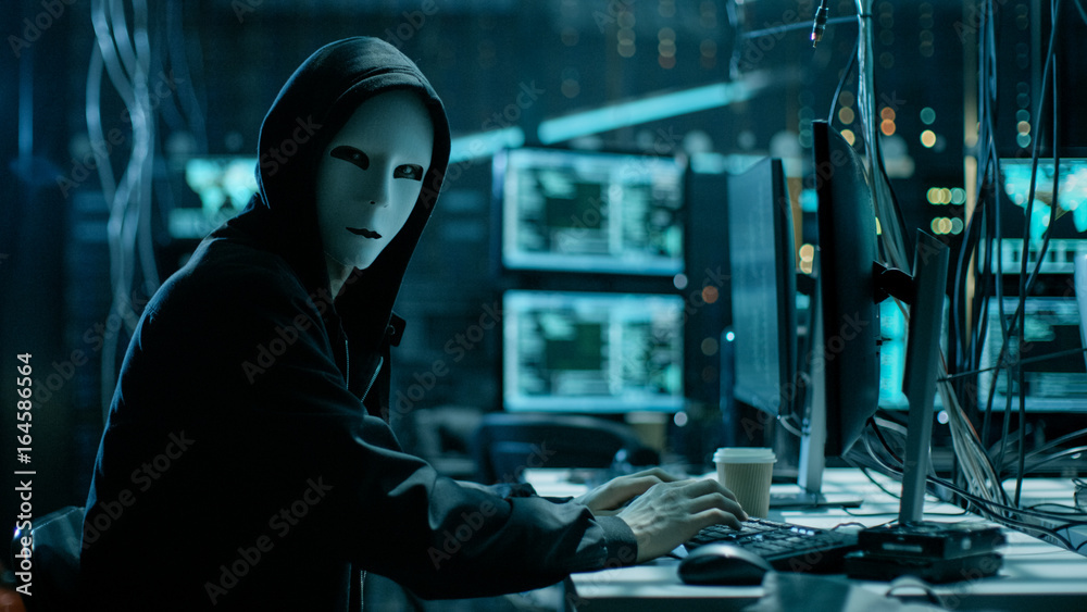 Fototapeta Masked Hacker is Using Computer for Organizing Massive Data Breach Attack on Corporate Servers. They're in Underground Secret Location Surrounded by Displays and Cables.