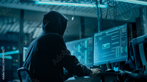 Fotografie, Tablou  Shot from the Back to Hooded Hacker Breaking into Corporate Data Servers from His Underground Hideout