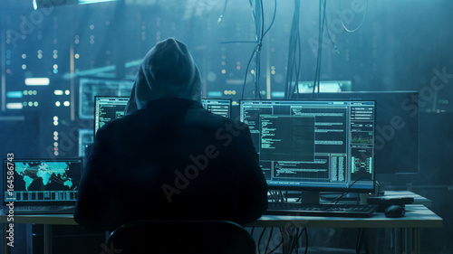 Dangerous Hooded Hacker Breaks into Government Data Servers and Infects Their System with a Virus. His Hideout Place has Dark Atmosphere, Multiple Displays, Cables Everywhere.