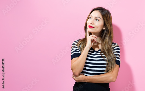 Photo Young woman in a thoughtful pose on a pink background