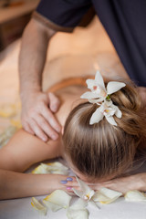 Obraz na płótnie Canvas Woman having massage in the spa salon. Body care. Flower in hair