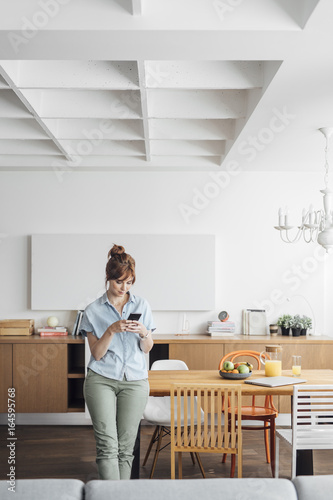 Beautiful ginger Caucasian woman standing at dining room at home and typing on cell phone.