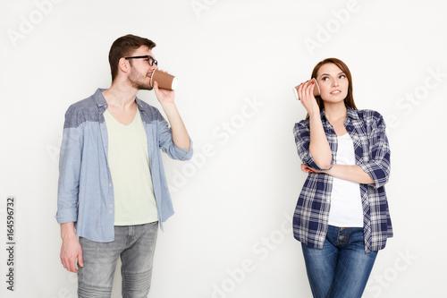 Young casual couple talking through tin can phone Tapéta, Fotótapéta