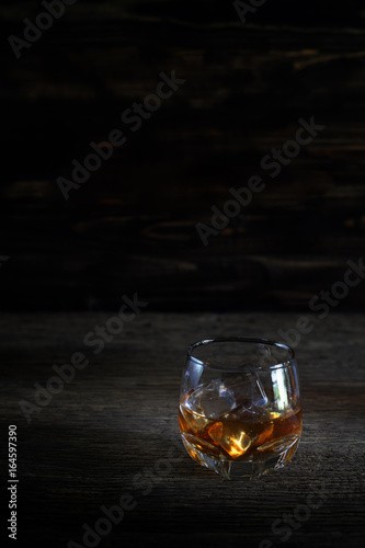 Glass of liquor on wooden floor in low light. Canvas Print