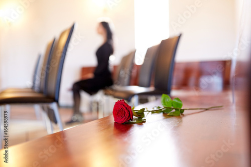 Fotografia red roses and woman crying at funeral in church