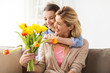 happy girl giving flowers to mother at home