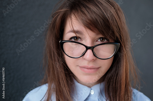 Fotografie, Obraz  Closeup portrait of young attractive woman with glasses on a dark background