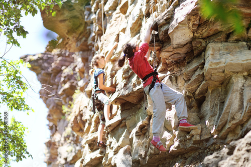 Girl teenager climbs on the rock pi aid equipment for rock climbing and mountaineering