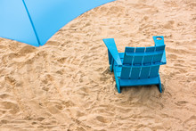 Aerial Closeup Of Blue Beach Chair And Umbrella On Sand Overlooking River Harbor During Sunset