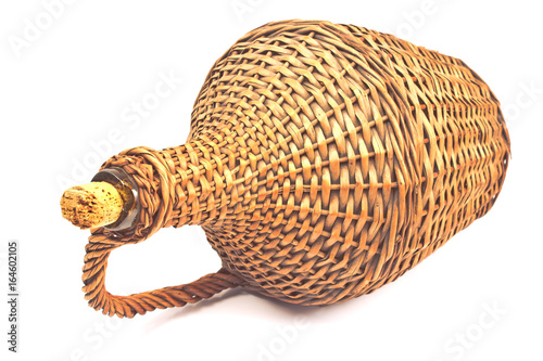 Tela Old demijohn wicker wrapped glass bottle isolated on white