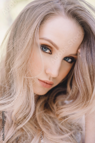 Studio Portrait of Beautiful Model with Volume Shiny Wavy Blond Hair. Fashion Make Up and Curly Ombre Hair. Close up