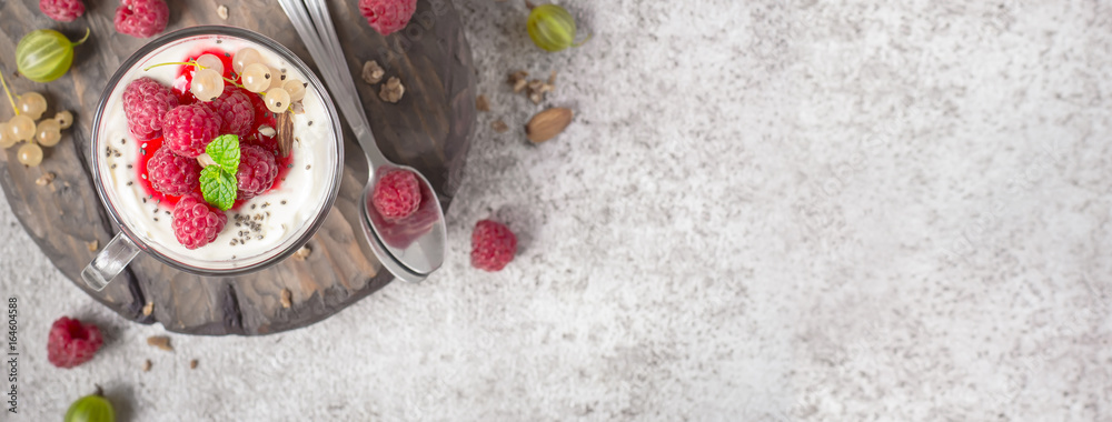 Fototapeta Summer healthy dessert with raspberries and yogurt on the cutting board. Banner format