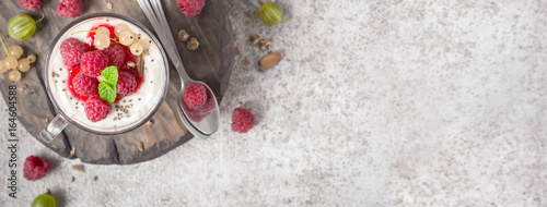 Photo Stands Dessert Summer healthy dessert with raspberries and yogurt on the cutting board. Banner format