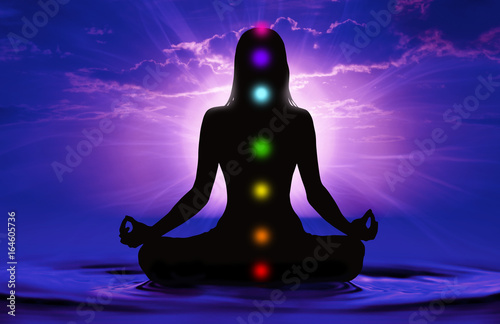 Fototapeta  Silhouette of woman doing yoga and where has scored seven chakra points