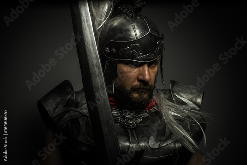 Fotografie, Obraz Gladiator, Roman centurion with armor and helmet with white chalk, steel sword a