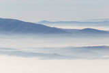 A view from above of a valley filled by a sea of fog, with various layers of emerging hills and mountains with different shades of blue - 164627385