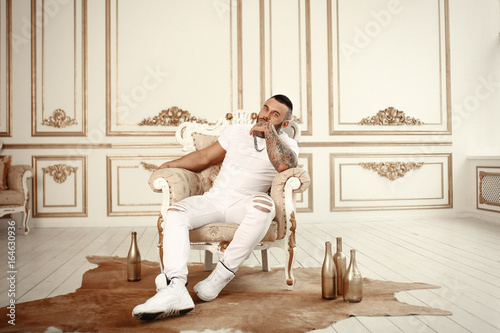 Pinturas sobre lienzo  Sexy closeup portrait of Elegant handsome male model with fashion tattoo and a black beard sitting in chair in white casual clothes in hotel interior with gold decor