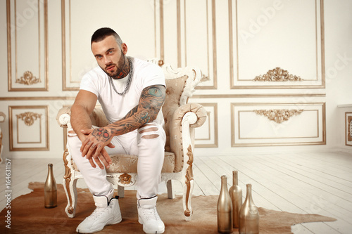 Fotomural  Sexy closeup portrait of Elegant handsome male model with fashion tattoo and a black beard sitting in chair in white casual clothes in hotel interior with gold decor