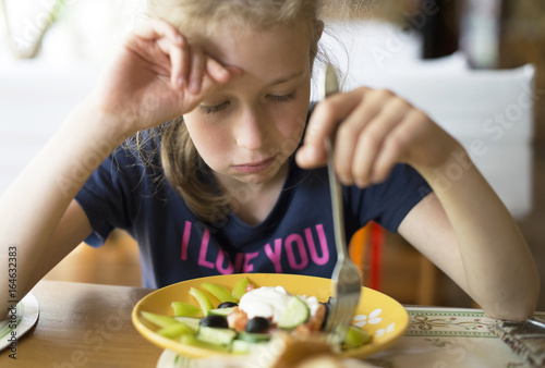 Valokuva  Little girl don't want to eat meal in restaurant.