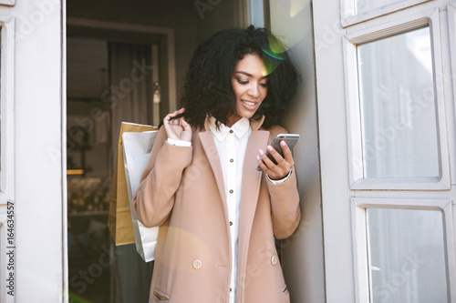 Fotografie, Obraz  Young African American girl with dark curly hair standing with shopping bags and phone in her hands