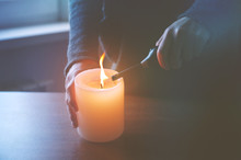 Hand Lighting Candle In Evening