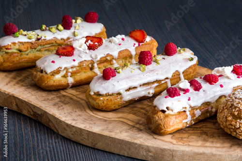 Fotografia Delicious eclairs with fruits and pistachio on a wooden olive board