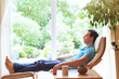 Leinwanddruck Bild - happy man relaxing in deck chair at home, wellbeing background, relaxation
