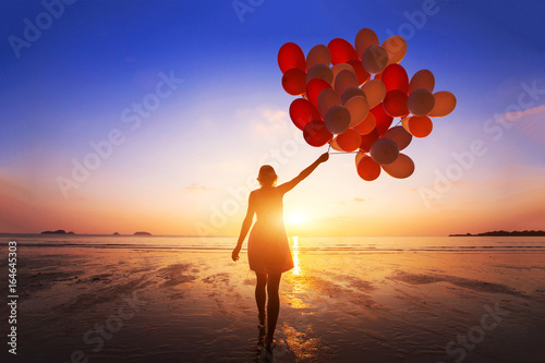 Fényképezés  inspiration, joy and happiness concept, silhouette of woman with many flying bal