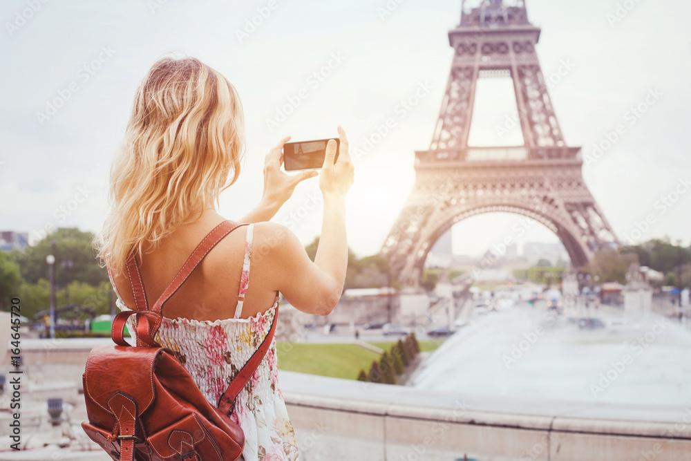 Fototapeta tourist in Paris visiting landmark Eiffel tower, sightseeing in France, woman taking photo on mobile phone